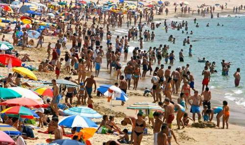 LAGOS, PORTUGAL - AUGUST 09: People sunbathe and swim at the beach a few minutes walk from the apartment where Madeleine McCann went missing in the resort of Praia da Luz on August 9, 2007 in the Algarve, Portugal. Police continue their investigation in the Algarve village after traces of blood were found in the McCann's holiday apartment. (Photo by Jeff J Mitchell/Getty Images)